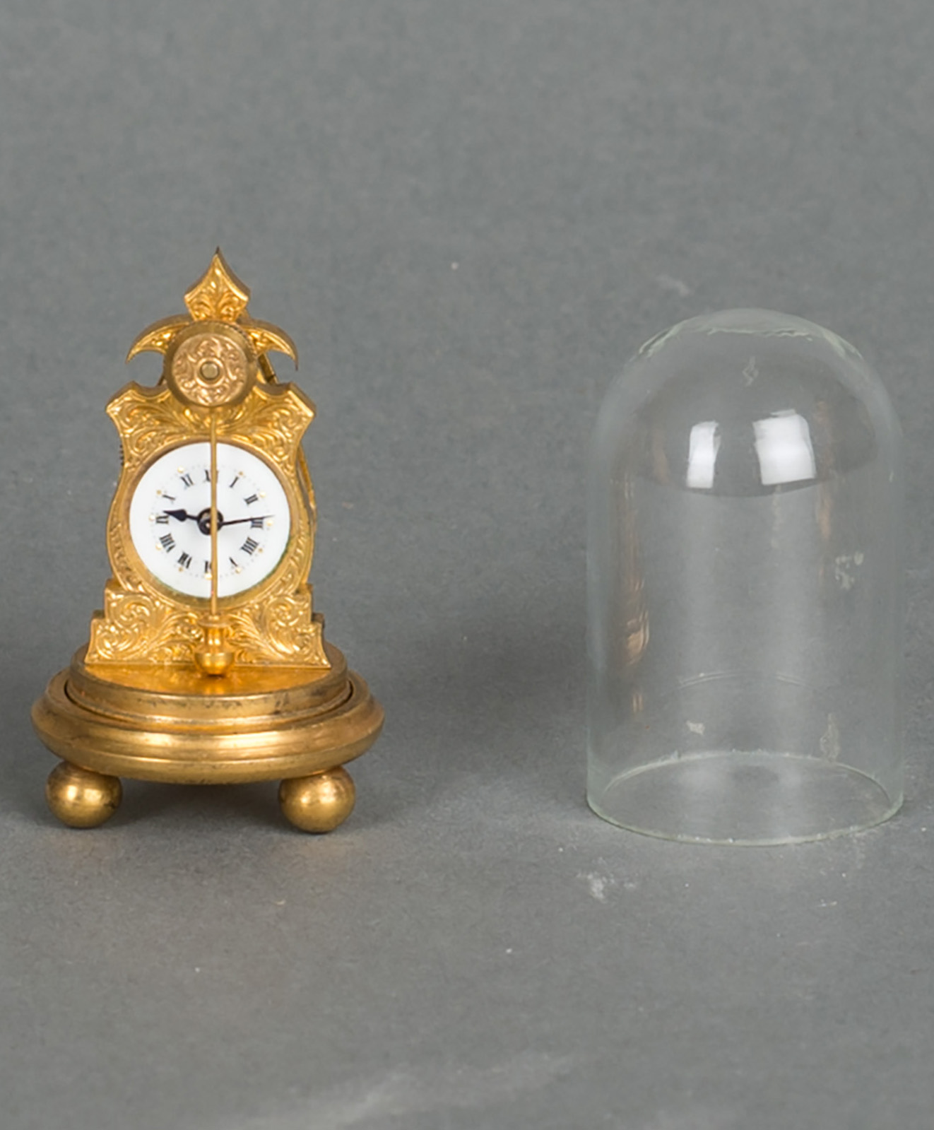 A very small and unusual Austrian ormolu zappler miniature clock with matching dome and enamel dial, circa 1860